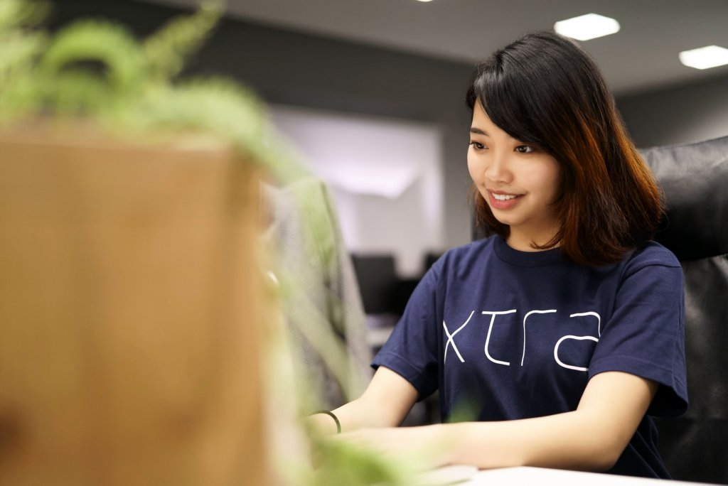 Asian woman typing and smiling