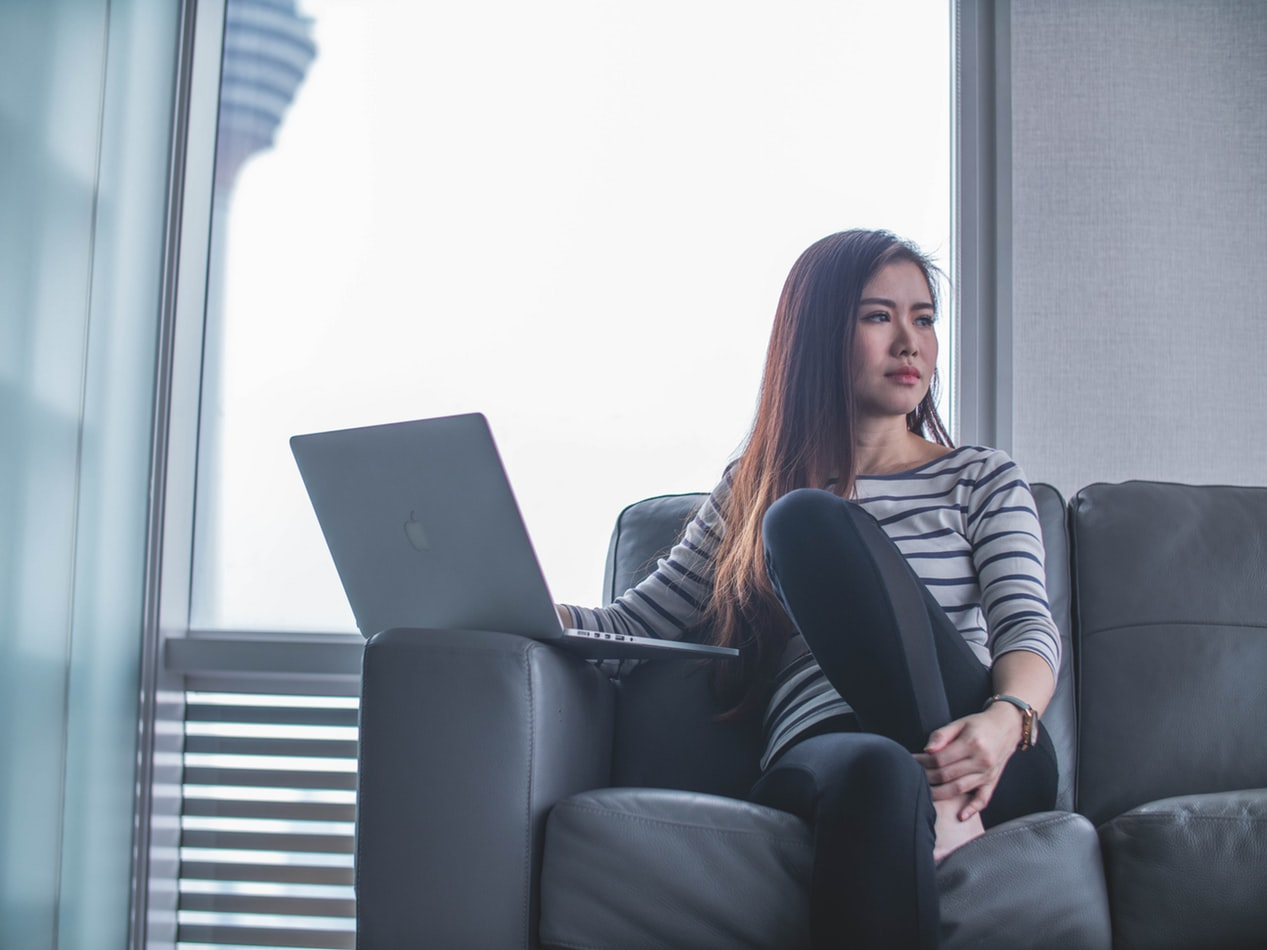 Asian woman on laptop sitting on couch