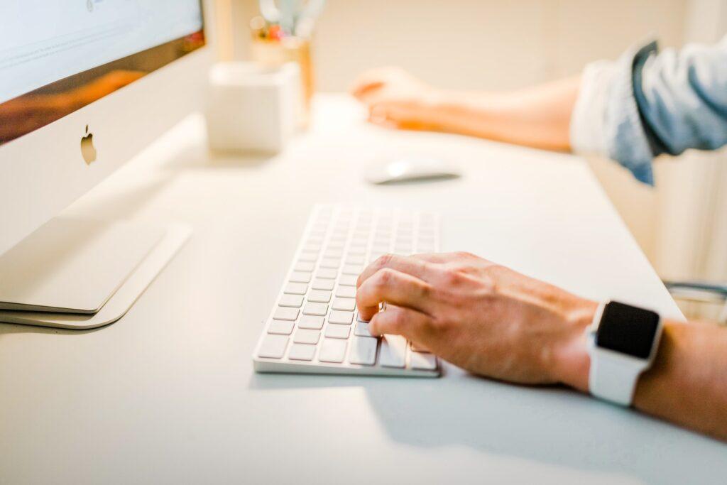 Man typing on white desk